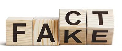 "Wooden blocks forming words ""Fact"" and ""Fake"""